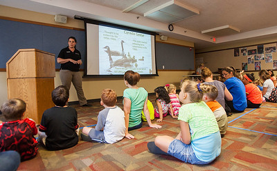 Kyle Grillot - kgrillot@shawmedia.com   Children and parents watch during the Animals of McHenry County presentation at the Crystal Lake Public Library given by McHenry County Conservation District Wildlife Resource Specialist Beth Gunderson Tuesday, July 23, 2013. The presentation gives children and parents the opportunity to learn more of the history of animals in the region as well as meet a special visitor, Rae the Blanding's turtle.