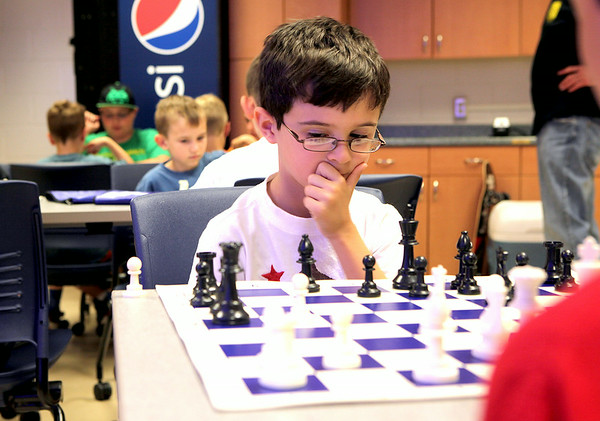 Aidan Cook contemplates his next move at chess camp hosted at Geneva High School. The camp taught students from 1st to 8th grade the basic moves and strategy of chess.