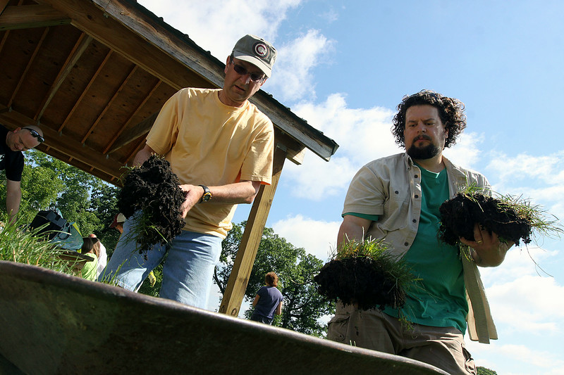 "Jeff Krage – For Shaw Media<br /> Ron Gaydos, left, of Geneva and Steve Sidor of St. Charles place grass into a wheelbarrow during Sunday's ""Jesus Has Left the Building"" day at Historic Corron Farm in Campton Hills. They are both members of The Congregational United Church of Christ in Campton Hills.<br /> Campton Hills 7/13/14"