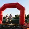 Jeff Krage – For Shaw Media<br /> Runners cross the finish line during the Summer Sunset 5K on Wednesday at Geneva High School.<br /> Geneva 7/29/15