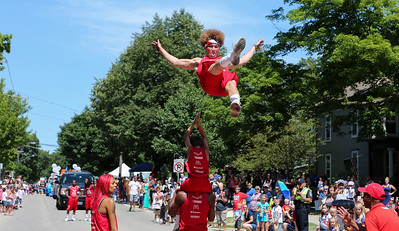 Mike Greene - For Shaw Media  A member of the Jessie White Tumblers flies through the air with his tongue out during the annual Crystal Lake Independence Day Parade Sunday, July 3, 2016 in Crystal Lake.