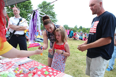 Mike Greene - For Shaw Media  Jamie Birchfield, left, helps Madison Knutson, 7, pick out a glow-in-the-dark item as father Richard Knutson  watches on during the annual Woodstock fireworks Monday, July 4, 2016 at Emricson Park in Woodstock.