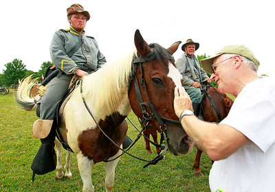 Candace H. Johnson Confederate soldiers, Joe Powell, 19, of Forest View and Kevin Wright, of Peotone, watch Mike Howell, of Arlington Heights pet Powell's horse, Jack, after the Battle of Big Bethel during Civil War Days at the Lakewood Forest Preserve in Wauconda.