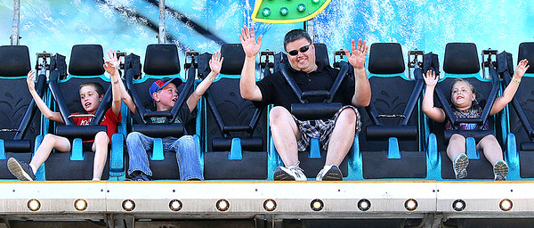 Candace H. Johnson Tyler Annarella, 8, and Brandon Marks, 9, both of Antioch, and Jim Padel, of Fox Lake Hills, and his daughter, Jillian, 7, keeps their hands up in the Moby Dick ride during the Antioch Taste of Summer in downtown Antioch.