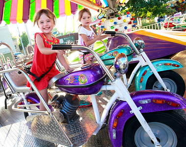 Candace H. Johnson McKenna Rice, 3, of Spring Grove is all smiles sitting next to her twin sister, Kailey, as they go on the motorcycle ride during the Antioch Taste of Summer in downtown Antioch.