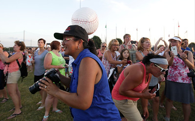 With a baseball pin her hat, Lisa Noonan, from Crystal Lake, takes photos during opening ceremonies for MCYSA 15-U baseball tournament at Lippold Park on Friday, July 22, 2016 in Crystal Lake. Noonan is with the Crystal Lake Babe Ruth team and is hosting Japanese players. John Konstantaras photo for the Northwest Herald