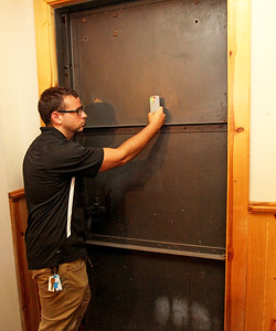 Candace H. Johnson-For Shaw Media Nick Sarlo, Shadow Hunters lead investigator, uses an EMF detector on a metal door to detect if spirits are present on the main floor of The Lodge of Antioch, a Northwoods Pub & Eatery, on Main Street. The metal door used to be in the basement to keep the police out of certain rooms where there were illegal activities.