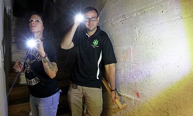 Candace H. Johnson-For Shaw Media Paranormal investigators Bekka Lieder and Nick Sarlo, with Shadow Hunters, look for spirits in the basement at The Lodge of Antioch, a Northwoods Pub & Eatery, on Main Street.