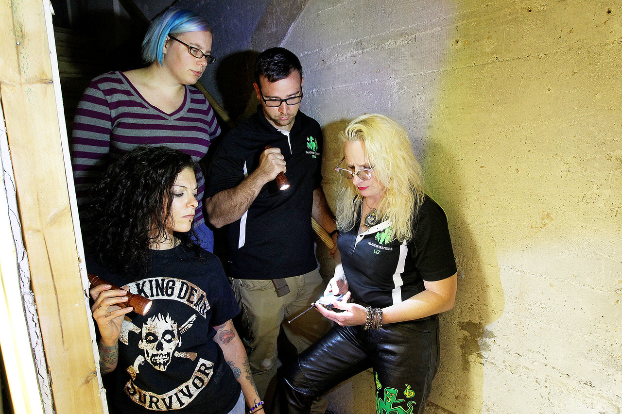 Candace H. Johnson-For Shaw Media Shadow Hunters Alexi Ragans-Stauffer, Nick Sarlo, and Bekka Lieder stand next to Liz Nygard as she looks at a spirit box in the staircase going down to the basement to see if any spirits are present at The Lodge of Antioch, a Northwoods Pub & Eatery, on Main Street.