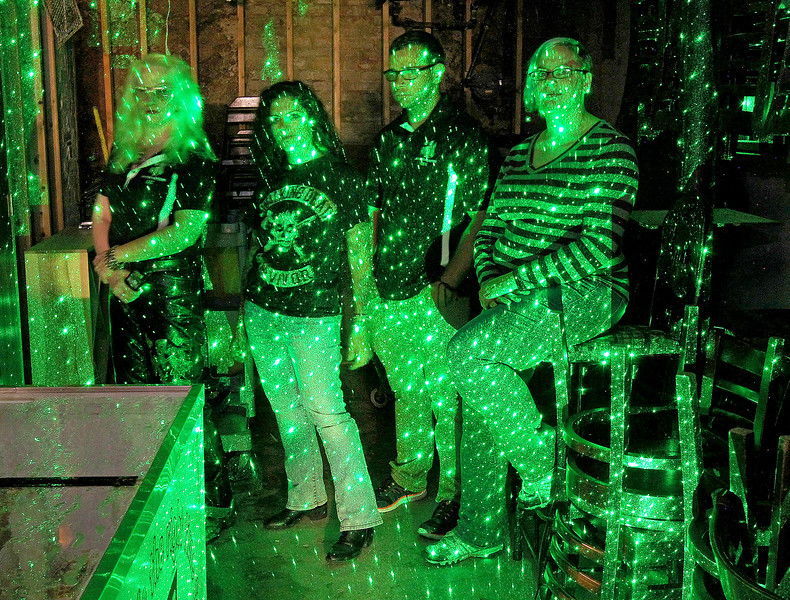 Candace H. Johnson-For Shaw Media Paranormal investigators Liz Nygard, Bekka Lieder, Nick Sarlo and Alexi Ragans-Stauffer, with Shadow Hunters project a laser grid onto the wall to see shadows as they stand in the store room of the basement under the bar at The Lodge of Antioch, a Northwoods Pub & Eatery, on Main Street.