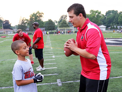 Candace H. Johnson-For Shaw Media Bryan Sassolino, 9, of Ingleside gets some throwing tips from Coach Christian Cazares during the Grant Bulldogs Youth Football Clinic at Grant Community High School.