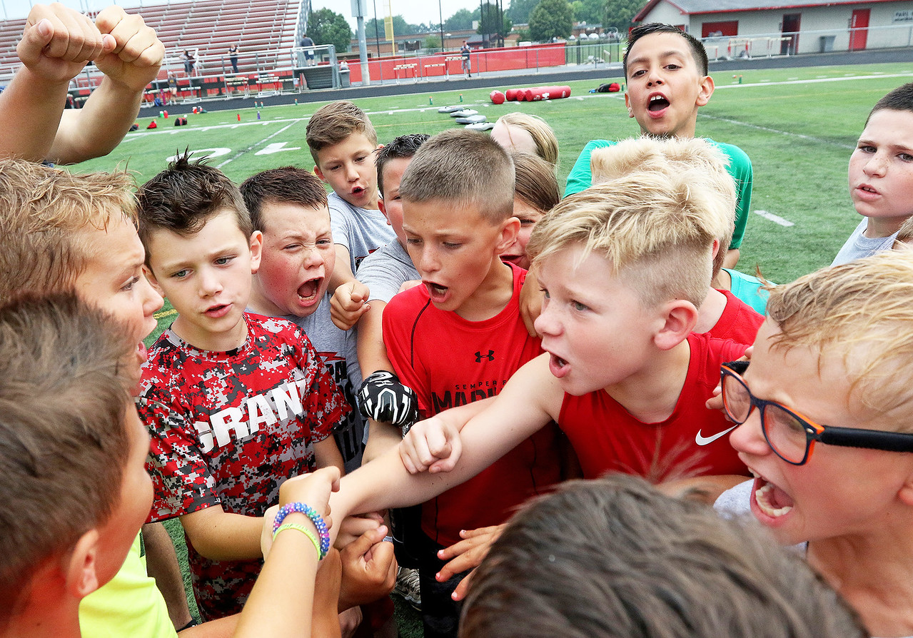 """Candace H. Johnson-For Shaw Media Football players call out, """"Bulldogs,"""" in a huddle during the Grant Bulldogs Youth Football Clinic at Grant Community High School."""