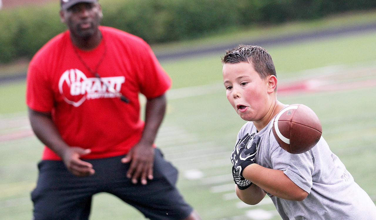 Candace H. Johnson-For Shaw Media Tony Sheron, assistant freshman coach, watches Jonathan Gersch, 9, of Fox Lake try to catch the ball during a receiver drill at the Grant Bulldogs Youth Football Clinic at Grant Community High School.