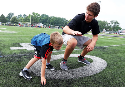 Candace H. Johnson-For Shaw Media Griffin Art, 6, of Round Lake learns stances from Tyler Cameron, 16, of Fox Lake during the Grant Bulldogs Youth Football Clinic at Grant Community High School. Cameron will play defensive end during the football season at Grant.