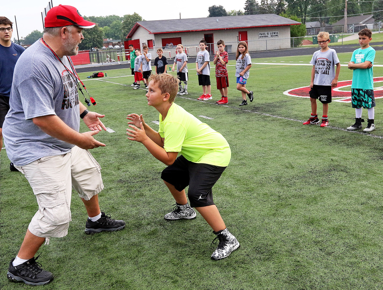 Candace H. Johnson-For Shaw Media John Jared, of Round Lake, president of the Grant Bulldogs Youth Football program, works with Jack Hembrey, 10, of Fox Lake on how to get down low for blocking during the Grant Bulldogs Youth Football Clinic at Grant Community High School.
