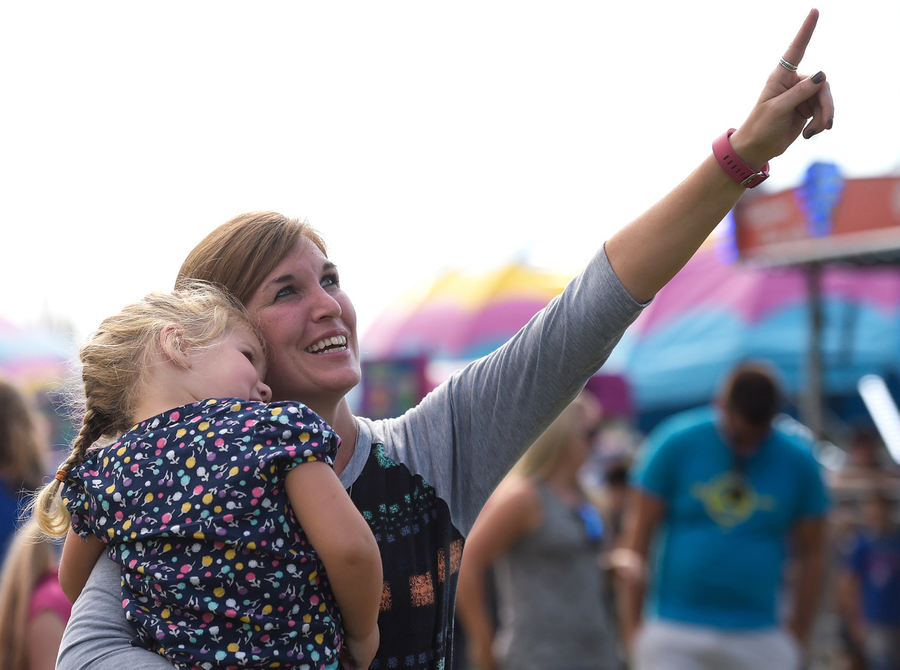 Kayla Wolf - for Shaw Media Michelle Fung points to her son on a ride while holding her daughter Gemma Fung, 3, Saturday, July 15, 2017, during Fiesta Days at Petersen Park.