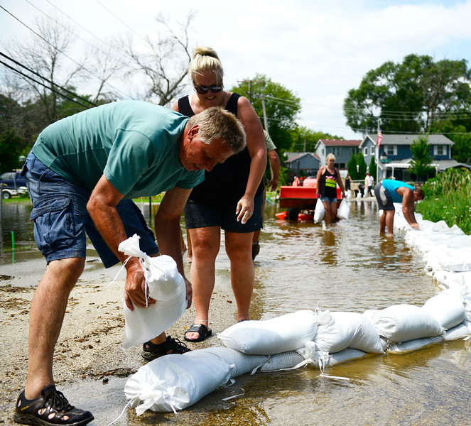 Kayla Wolf - for Shaw Media Pete Rieder places a sandbag along Northeast Shore Dr   on Saturday, July 15, 2017. The residents along Northeast Shore Dr back up to Lake Griswold.