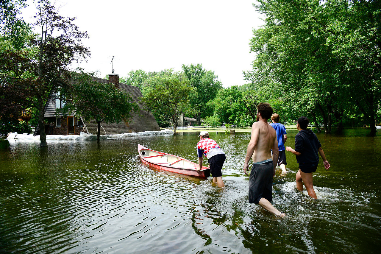 Kayla Wolf - for Shaw Media Ross Anderson pushes a canoe full of sandbags towards the house of Pamela and Ben Berger Saturday, July 15, 2017.  Water is surrounding the house and detached garage on all sides.