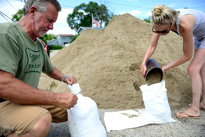 Kayla Wolf - for Shaw Media Residents Jim Dunne and Amanda Heil fill sandbags Saturday, July 15, 2017, along Northeast Shore Dr in Holiday Hills. Friends and neighbors helped sandbag along the road to keep water from flooding basements, crawlspaces and septic fields.