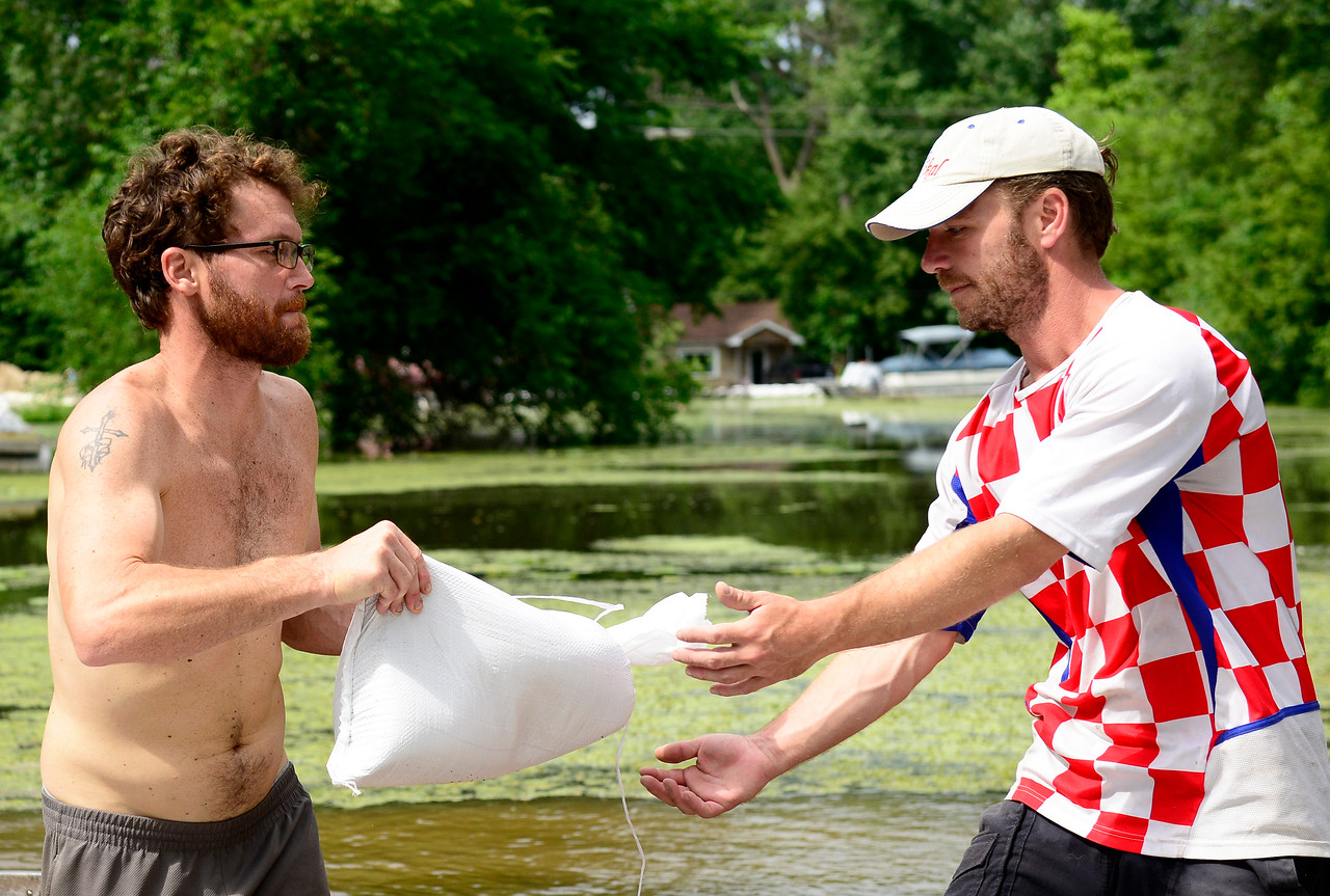 Kayla Wolf - for Shaw Media Ben Berger, left, hands a sandbag to Ross Anderson Saturday, July 15, 2017, along a channel of the Fox River. Flood levels are anticipated to exceed 2013 levels.