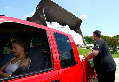 Kayla Wolf - for Shaw Media Morgan Armbruster waits as sandbags are loaded into the truck at Nunda Township Highway Department Saturday, July 15, 2017. Volunteers at the highway department filled sandbags with a sandbag machine that could fill four sandbags at a time.