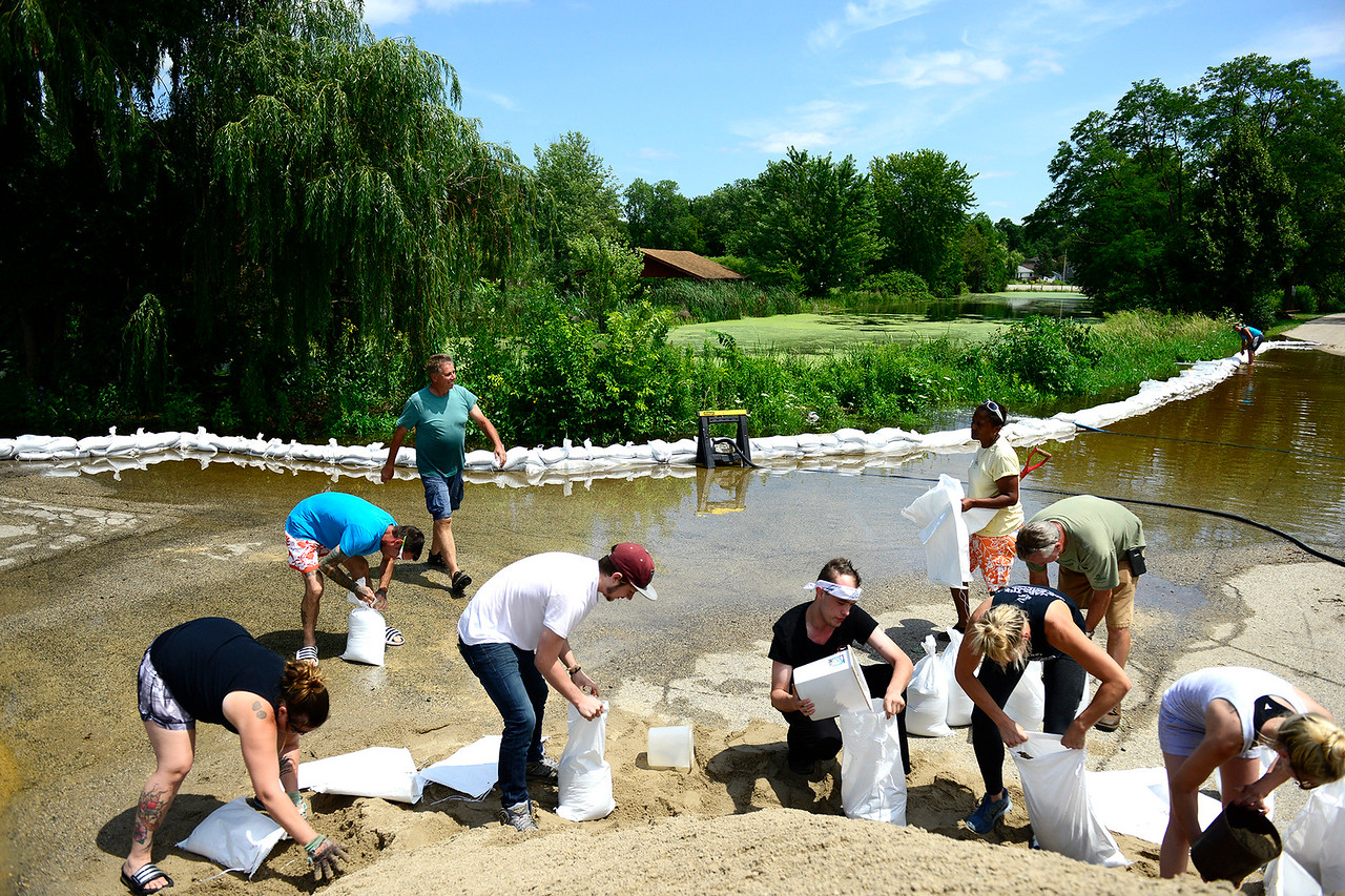 Kayla Wolf - for Shaw Media Residents that live along Northeast Shore Dr in Holiday Hills, which backs up to Griswold Lake, fill sandbags Saturday, July 15, 2017. Friends and neighbors helped sandbag along the road to keep water from flooding basements, crawlspaces and septic fields.