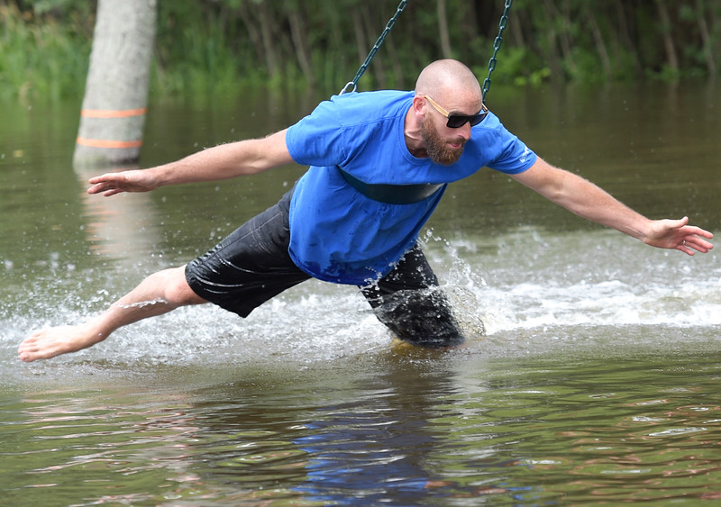 Kayla Wolf - for Shaw Media Will Barnett uses a swing to glide over the water Sunday, July 16, 2017, while taking a break from stacking sandbags. Family and friends had been stacking sandbags since Thursday.
