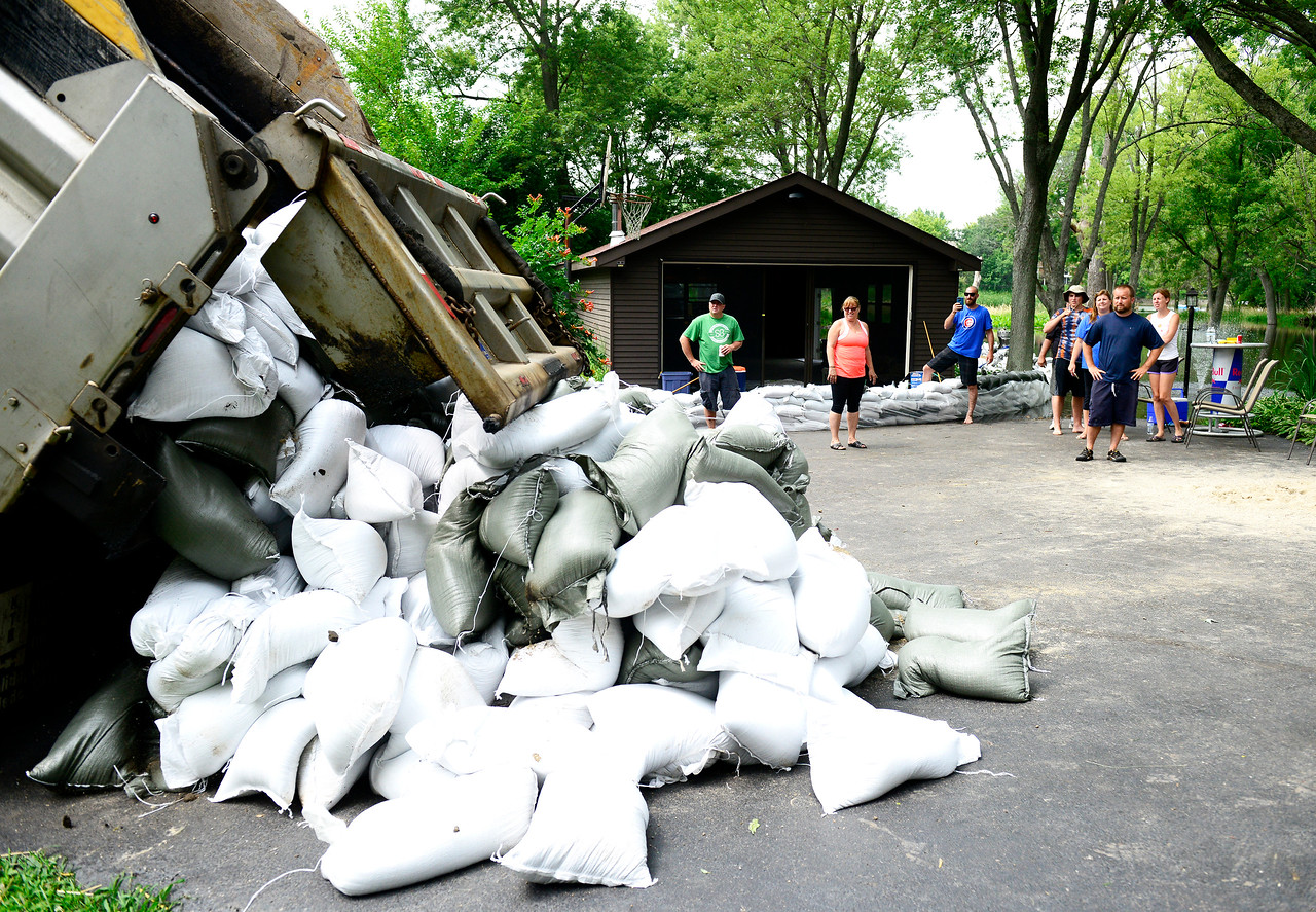 Kayla Wolf - for Shaw Media Friends, neighbors and family watch Sunday, July 16, 2017 as sandbags are unloaded by Nunda Township to the house of Steve Gunn. The house is located on the Fox River in Fox River Grove.