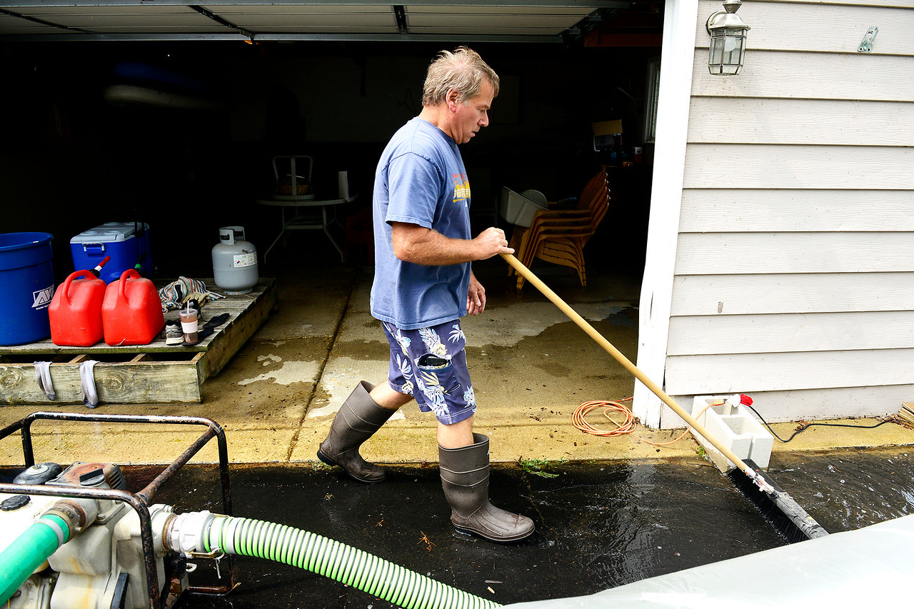 Kayla Wolf - for Shaw Media Doug McAllister pushes water from his garage towards a pump Sunday, July 16, 2017, to move the water away from his house. McAllister bought the house on July 7 and moved in, but five days later they moved all of their stuff out and stored it back at their primary residence in Crystal Lake.