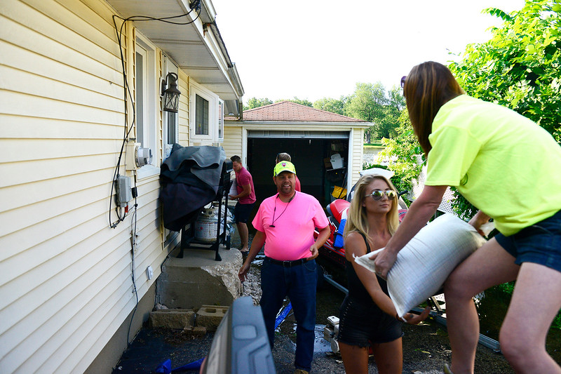 Kayla Wolf - for Shaw Media Algonquin Township Trustee Rachel Lawrence hands a sandbag to Kelsey Christensen Sunday, July 16, 2017.  Algonquin Township Highway Commissioner Andrew Gasser, center, and Lawrence of Algonquin Township Highway Department helped unload these sandbags in Fox River Grove.