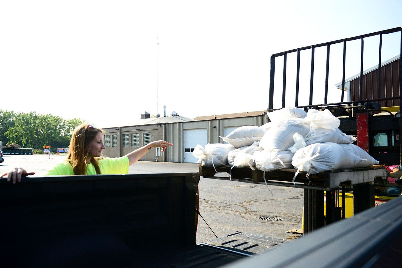 Kayla Wolf - for Shaw Media Algonquin Township Trustee Rachel Lawrence gives direction to Algonquin Township Highway Commissioner Andrew Gasser on Sunday, July 16, 2017, as they load a pallet of sandbags into his truck. The two drove around and delivered sandbags to people who needed them.