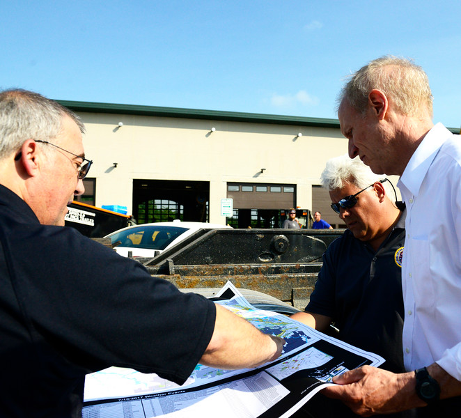 Kayla Wolf - for Shaw Media From left, Emergency Management Coordinator for McHenry County Dave Christensen, Gov. Bruce Rauner and McHenry County Board Chairman Jack Franks look at a map of projected flooding Sunday, July 16, 2017. The Fox River reached major flooding stage in McHenry and Algonquin on Sunday.