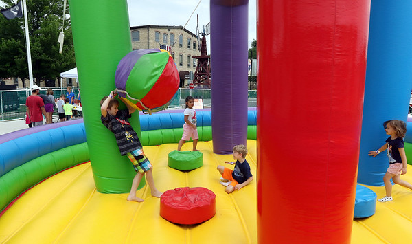 Children play on an inflatable during the Windmill City Festival at the Batavia Riverwalk July 16.