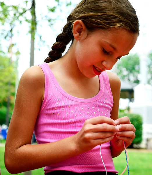 Kayla Wolf - for Shaw Media Kendra Norris makes a bracelet Sunday, July 16, 2017 at the Woodstock Folk Festival.  Eight musical acts rounded out the main stage schedule and families picnicked in the Historic Woodstock Square during the festival.