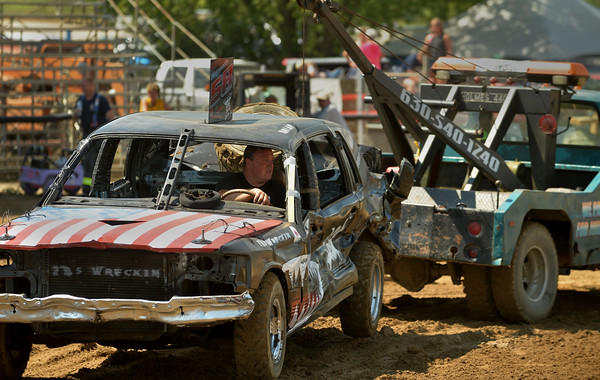 Demolition Derby competitor Brian Ellingsworth of Bolingbrook gets a tow back to the pits after a heat July 23 at the Kane County Fair in St. Charles.