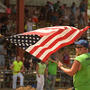 "Buddy Johnson of St. Charles waves the flag during the ""Star Spangled Banner"" before demolition derby action begins July 23 at the Kane County Fair in St. Charles."
