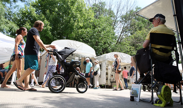 People stroll through the Geneva Art Fair along Third Street July 22.