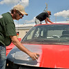 Joe Jackson, front, of St. Charles helps Paul Reid of Genoa paint his Demolition Derby car before heats begin July 23 at the Kane County Fair in St. Charles.