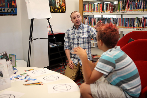 Sugar Grove Public Library Adult Services Assistant Tim Fitzpatrick (left)  explains how to structure a story to Brayden Cattero (right), 11, during a meeting of the Young Filmmakers Club at the library.