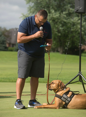 "Army veteran Charles ""Cookie"" Dalgo and his service dog Marshall lead a prayer during a fundraiser for Warrior Wishes at Royal Hawk Country Club in St. Charles July 24. The St. Charles non-profit grants veterans wishes to attend sporting events around the country."