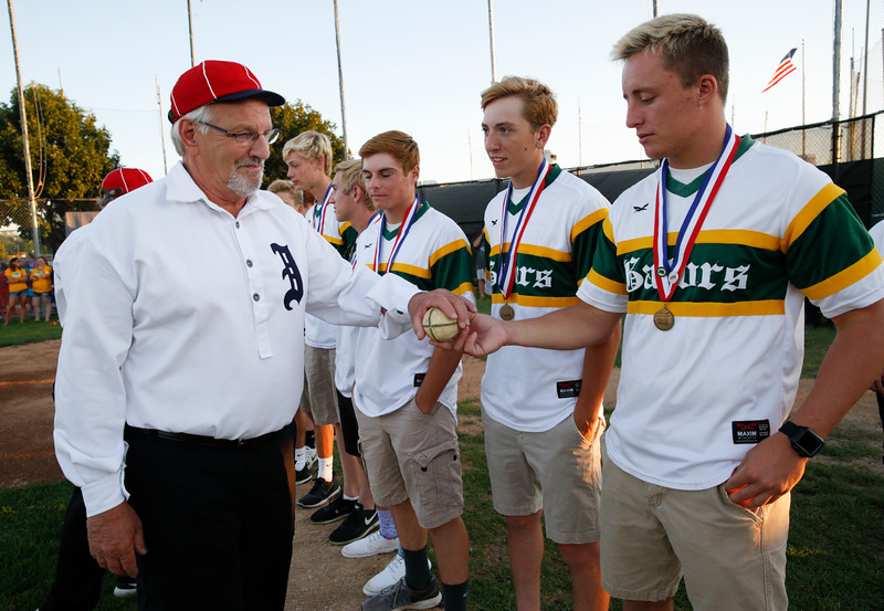 """A member of the Independents, a Civil War era baseball team from the McHenry County Historical Society shows a """"lemon ball"""" to Michael Swiatly with the Crystal Lake South baseball team during the MCYSA international baseball tournament's opening ceremony at Lippold Park on Thursday, July 27, 2017 in Crystal Lake, Illinois. The Crystal Lake South baseball team was honored for their IHSA Class 4A Championship during the ceremony. John Konstantaras photo for the Northwest Herald"""
