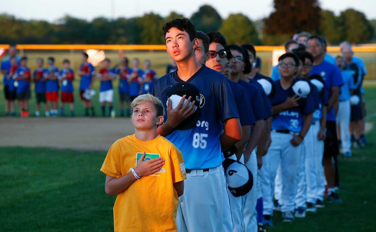 Landon Creighton, 11 from Woodstock, stands with Enzo Paes and the Brazilian baseball team during their national anthem during the MCYSA international baseball tournament's opening ceremony at Lippold Park on Thursday, July 27, 2017 in Crystal Lake, Illinois. John Konstantaras photo for the Northwest Herald