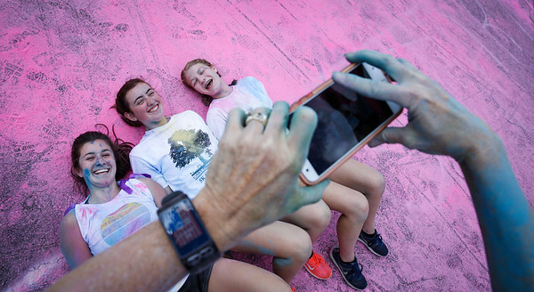 Ann Coles, right, takes a photo of Cary-Grove Varsity Dance members (L-R) Madelyn Coles, 14 from Cary, Laura Michie, 15 from Fox River Grove, and Jill Kraeger, 15 from Cary, after the Cary Park District 5K Color Run on Saturday, July 29, 2017 in Cary, Illinois. John Konstantaras photo for the Northwest Herald