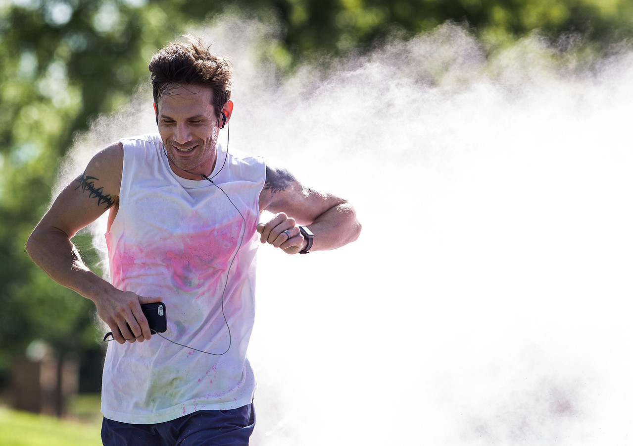 Jason Ruh, from Cary, avoids a pink cloud of powder as he is the first to cross the finish line during the Cary Park District 5K Color Run on Saturday, July 29, 2017 in Cary, Illinois. John Konstantaras photo for the Northwest Herald