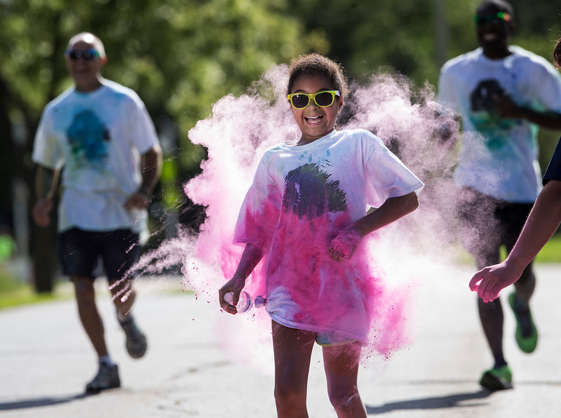 Acamaya Bailey, 11 from Cary, runs through a cloud of pink powder as she finishes the Cary Park District 5K Color Run on Saturday, July 29, 2017 in Cary, Illinois. John Konstantaras photo for the Northwest Herald