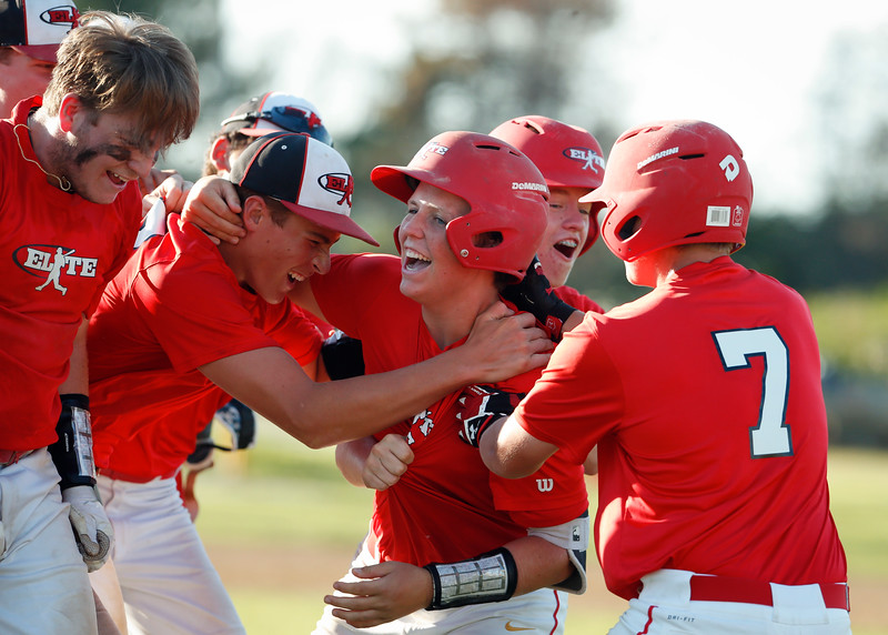 Elite Baseball Training's Noah Burgh (center) is mobbed by his teammates after hitting the game winning walkoff RBI in the seventh inning of their 15u championship game against the Crystal Lake Cardinal during the MCYSA International Baseball Tournament at Lippold Park on Sunday, July 30, 2017 in Crystal Lake, Illinois. Elite Baseball Training defeated the Crystal Lake Cardinals 6-5. John Konstantaras photo for the Northwest Herald