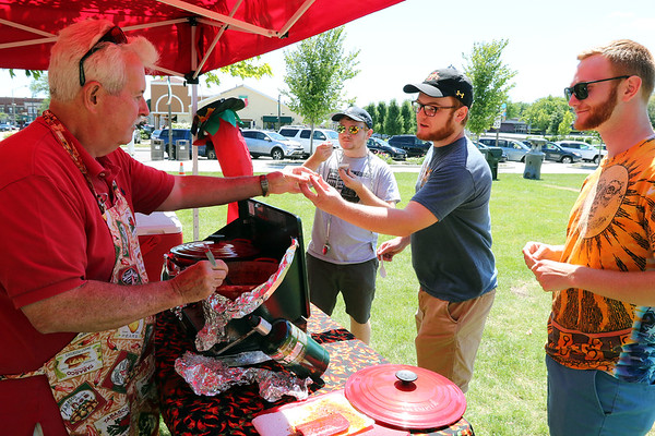 Lyle Cunningham, left, of Metamora serves chili to the Pohorski brothers of Batavia, left to right, Matt, Nick and Charlie, during the 25th annual Illinois State Championship Chili Cook-Off hosted by the Batavia Park District and Batavia Chamber of Commerce at the Batavia Riverwalk July 29.