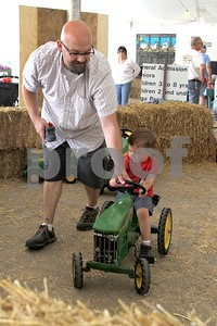 Brandon Parker helps his son, James, 2, steer the pedal tractor at the DuPage County Fair on Saturday, July 29, 2017. Sarah Minor for Shaw Media