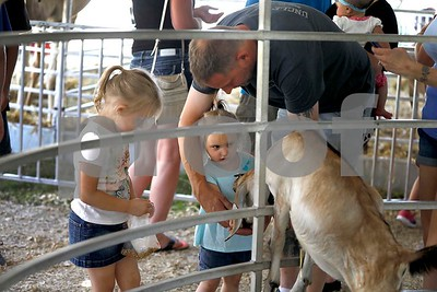 Mike Gunther of West Chicago helps his daughters Justice, 4, and Karma, 2, Saturday, July 29, 2017 feed the goats at the petting zoo at the DuPage County Fair. Sarah Minor for Shaw Media