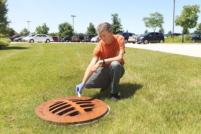 Candace H. Johnson-For Shaw Media Mike Adam, senior biologist, holds a larvicide pellet he is about to put into a storm drain with standing water to kill mosquito larvae on the property of the Lake County Central Permit Facility in Libertyville.The pellet will last 150 days. (7/2/18)